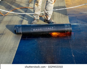 "Worker preparing part of bitumen roofing felt roll for melting by gas heater torch flame. On the back of the sheath there is the stamp ""Made in Italy"" product."