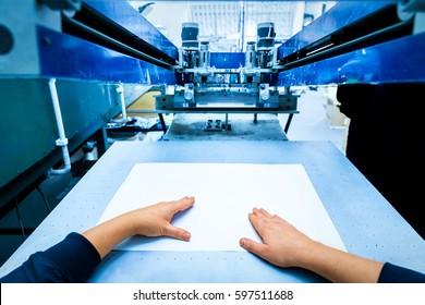 Worker preparing print screening metal machine. Industrial printer. Manufacture work. First person perspective.
