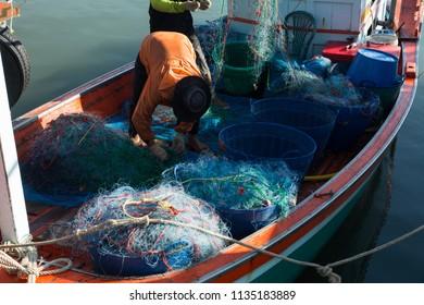 Worker preparing trawl in the boat