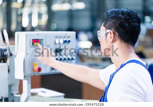 Arbeiter-Druckknöpfe auf CNC-Maschinensteuerbrett in asiatischen Fabriken