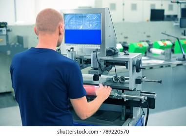 Worker in a printing and press center uses plate mounting machine to attach polymer relief plate on a printing cylinder. Scene showing manual mounting of printing plate for flexographic print machine.