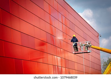 worker of Professional Facade Cleaning Services washing the red wall. Worker wearing safety harness washes wall facade at height on modern building in a crane.