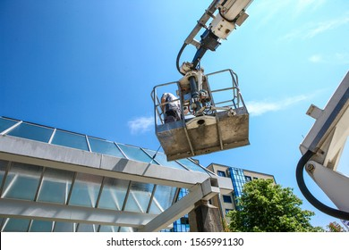 worker of Professional Facade Cleaning Services washing a galss roof
