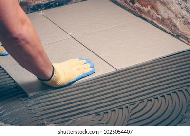 The worker professionally puts the tile on the floor, tiling the bathroom