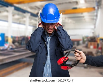 Worker protecting his ears from the noise