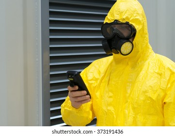 Worker in protective chemical suit checking radiation with geiger counter.