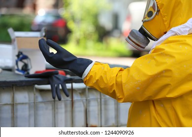 worker with protective clothing puts gloves on