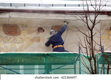 The worker in protective glasses and a respirator processes the wall with an angle grinder before restoration and plastering
