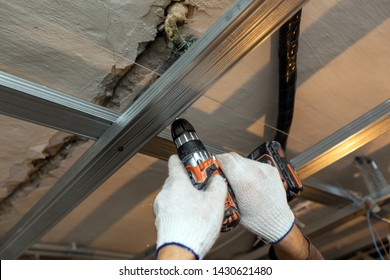 Worker with protective gloves is drilling by perforator the ceiling for installing metall frames in apartment that is under construction, remodeling, renovation, overhaul, extension, restoration and