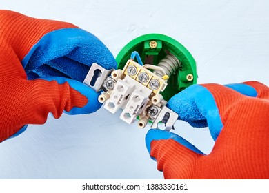 Worker in protective gloves is mounting european standard double switch placed in the socket.