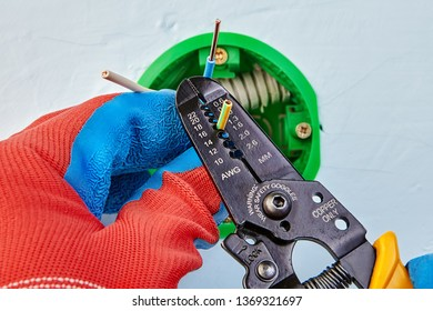 Worker in protective gloves  is removing insulation from wires of round outlet box with wire stripper tool.