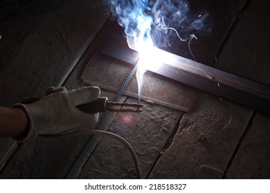a worker with protective gloves welding metal and sparks