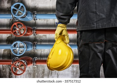 worker with protective helmet in front of industrial refinery oil pipes with valves