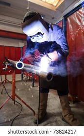 Worker with protective mask weld metal in industrial environment and sparks spread