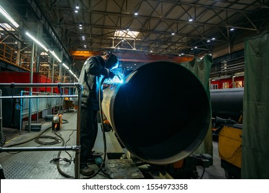 Worker in protective mask welding pipe in factory