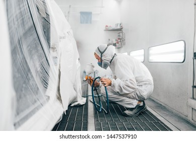 Worker in protective uniform painting a car in a paint booth.