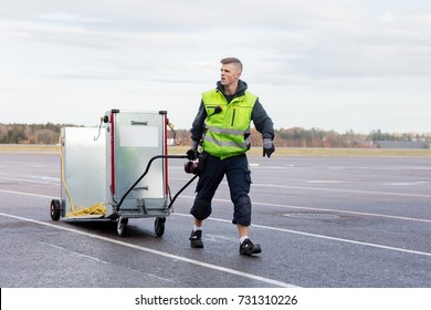 Worker Pulling Machine On Cart At Airport Runway