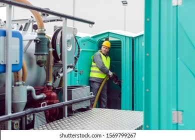 Worker pumping feces out of rental toilet for disposal and cleaning