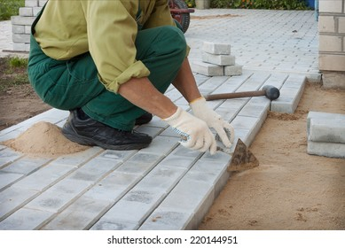 Worker puts the blocks, creating a sidewalk