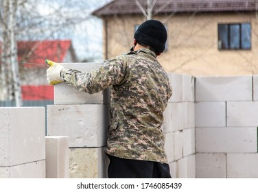 Worker puts foam concrete bricks into the wall. Building a house.