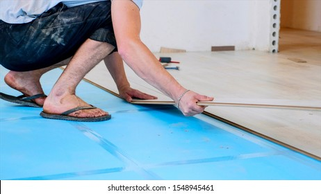 A worker is putting laminate panels together in the light room, the process of flooring. Legs and arms in shot, stands up and goes away.