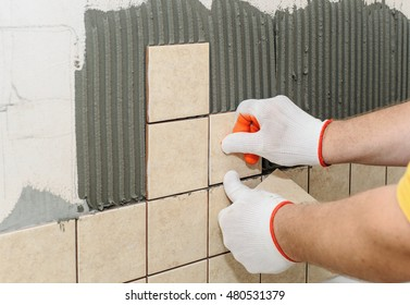 Worker putting  tiles on the wall in the kitchen. His hands are placing the tile on the adhesive.