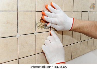 Worker putting tiles on the wall in the kitchen. His hands  inserting the crosses between the tiles to align rows.