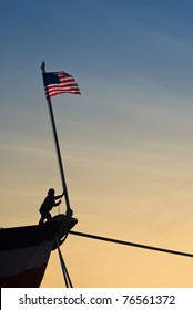 Worker raises American flag on bow of ship