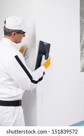 Worker rasping the corners of insulation panels