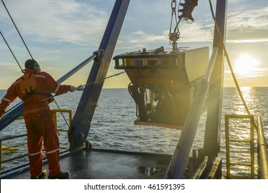 worker recovering robotics Remote Operated Vehicle (ROV) after entering sea surface during oil and gas pipeline inspection in the middle of South China Sea isolated on sunrise with glare