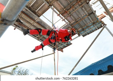 Worker with red boiler suit work at height low down by rope access