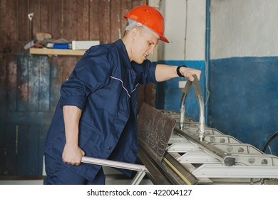 Worker in red cup and uniform working on the machine for cutting metal sheets