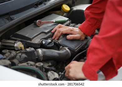 Worker in red overalls thinking over car engine