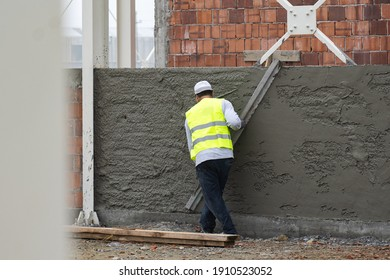 Worker in a reflective jacket leveling a plaster wall.