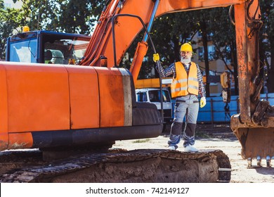 Worker in reflective vest and hardhat posing with excavator at construction site