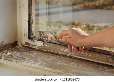 Worker removing oil window glazing putty using putty knife tool, old window restoration