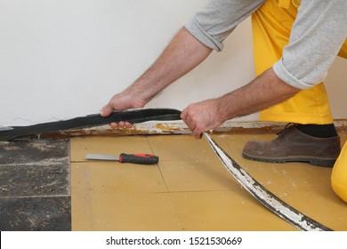Worker removing old batten and vinyl tiles from kitchen floor