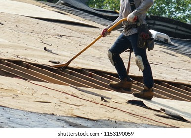 worker removing old shingle on the roof of the house for roof repair