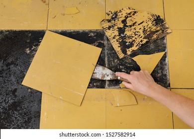 Arbeiter, der alte Vinyl-Fliesen aus dem Küchenboden entfernt, mit Spateltuchwerkzeug