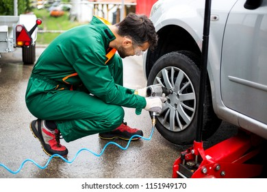 Worker removing tire from car