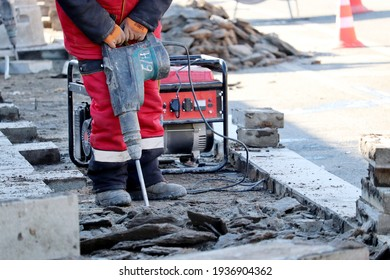 Worker repair the road surface with a jackhammer. Construction work, laying of paving slabs in city