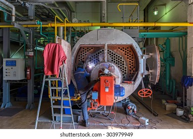 Worker repairing the boiler with the aid of welding