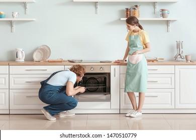 Worker repairing oven in kitchen