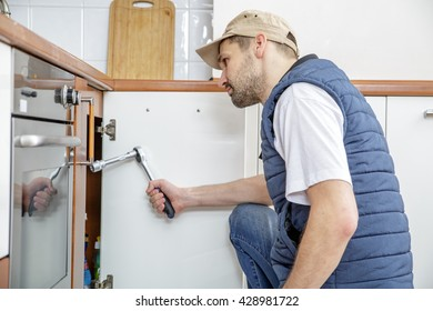 Worker repairing the sink in the kitchen. Man looks at the sink and holding a wrench.