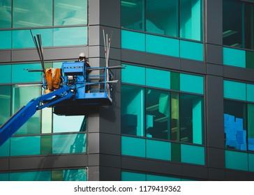 Worker repairing windows on highrise office building.