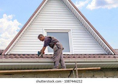 The worker repairs the roof of the cottage