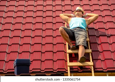 worker resting in the sun on the stairs on the roof of the house, against the background of tiles