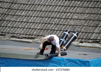 Worker with roll of bitumen on roof