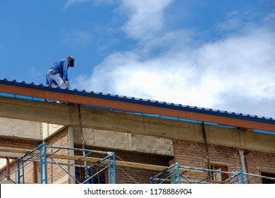 worker is roofing on tall building