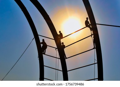 Worker rope access inspection of bridge railing. Risky worker with sunset background. Chattogram, Bangladesh / 2018.